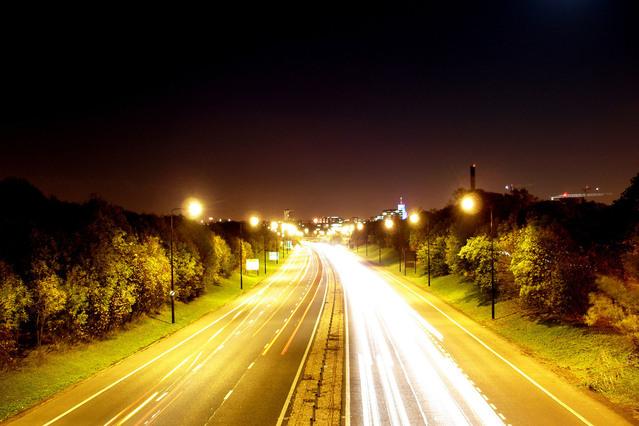Dálnice v obou směrech v noci, svítí pouliční světla, kolem cesty jsou stromy