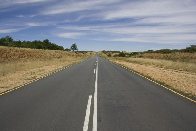 Silnice ve dne, suchá tráva, kolem v dáli stromy